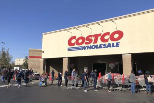 FILE - In this March 20, 2020 file photo, shoppers line up to enter a Costco store in Tacoma, Wash. Americans are beginning to see the first economic impact payments hit their bank accounts this week. The IRS tweeted Saturday, April 11, 2020, that it had begun depositing funds into taxpayers,Ao bank accounts and would be working to get them out as fast as it can.  (AP Photo/Ted S.