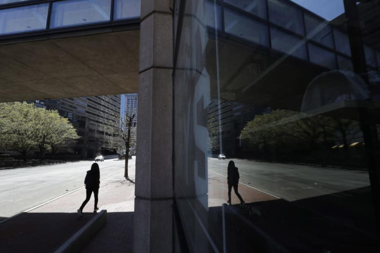 A person walks along a nearly empty street Wednesday, April 29, 2020, in Boston. Job cuts have escalated across the U.S. economy in recent days that remains all but shut down due measures taken to halt the spread of the virus.