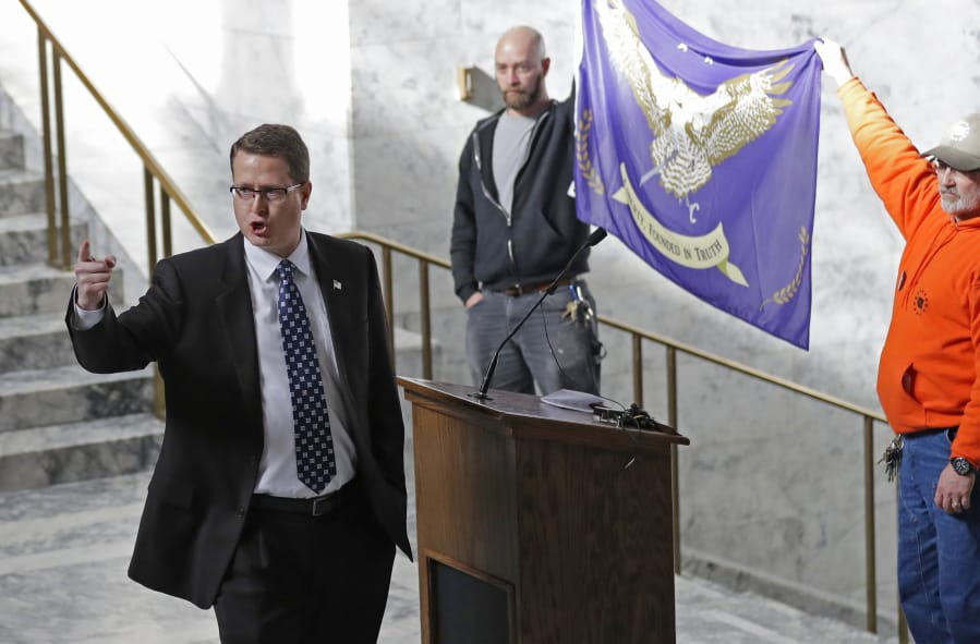 FILE - In this Friday, Feb. 15, 2019 file photo, Washington state Rep. Matt Shea, R-Spokane Valley, gestures as he gives a speech in front of the liberty state flag at the Capitol in Olympia, Wash., during a rally held by people advocating splitting Washington state into two separate states and questioning the legality of Washington's I-1639 gun-control measure. Prominent state lawmaker Shea says the coronavirus is a foreign bio-weapon and claims Marxists are using the pandemic to advance totalitarianism. (AP Photo/Ted S.