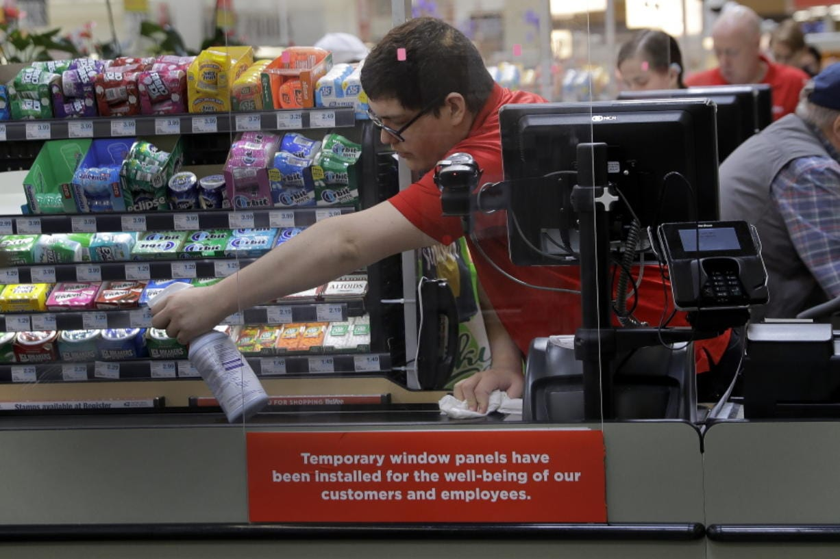 FILE - In this March 26, 2020, file photo, Garrett Ward sprays disinfectant on a conveyor belt between checking out shoppers behind a plexiglass panel at a Hy-Vee grocery store in Overland Park, Kan. From South Africa to Italy to the U.S., grocery workers -- many in low-wage jobs -- are manning the front lines amid worldwide lockdowns, their work deemed essential to keep food and critical goods flowing.