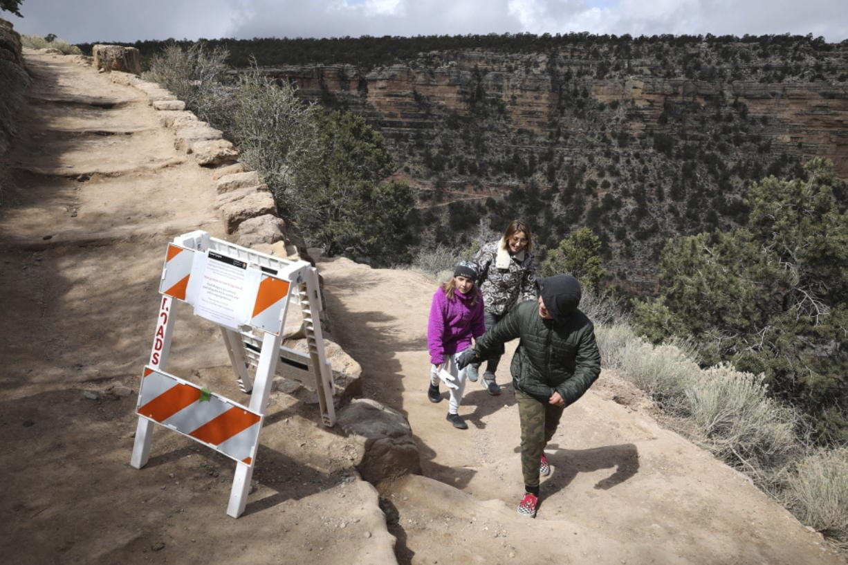 Shelly Clayton, center, walks up the Bright Angel Trail March 27 at Grand Canyon National Park, Ariz., with her children Audrey Kuhar, 11, left, and Cooper Kuhar, 11.