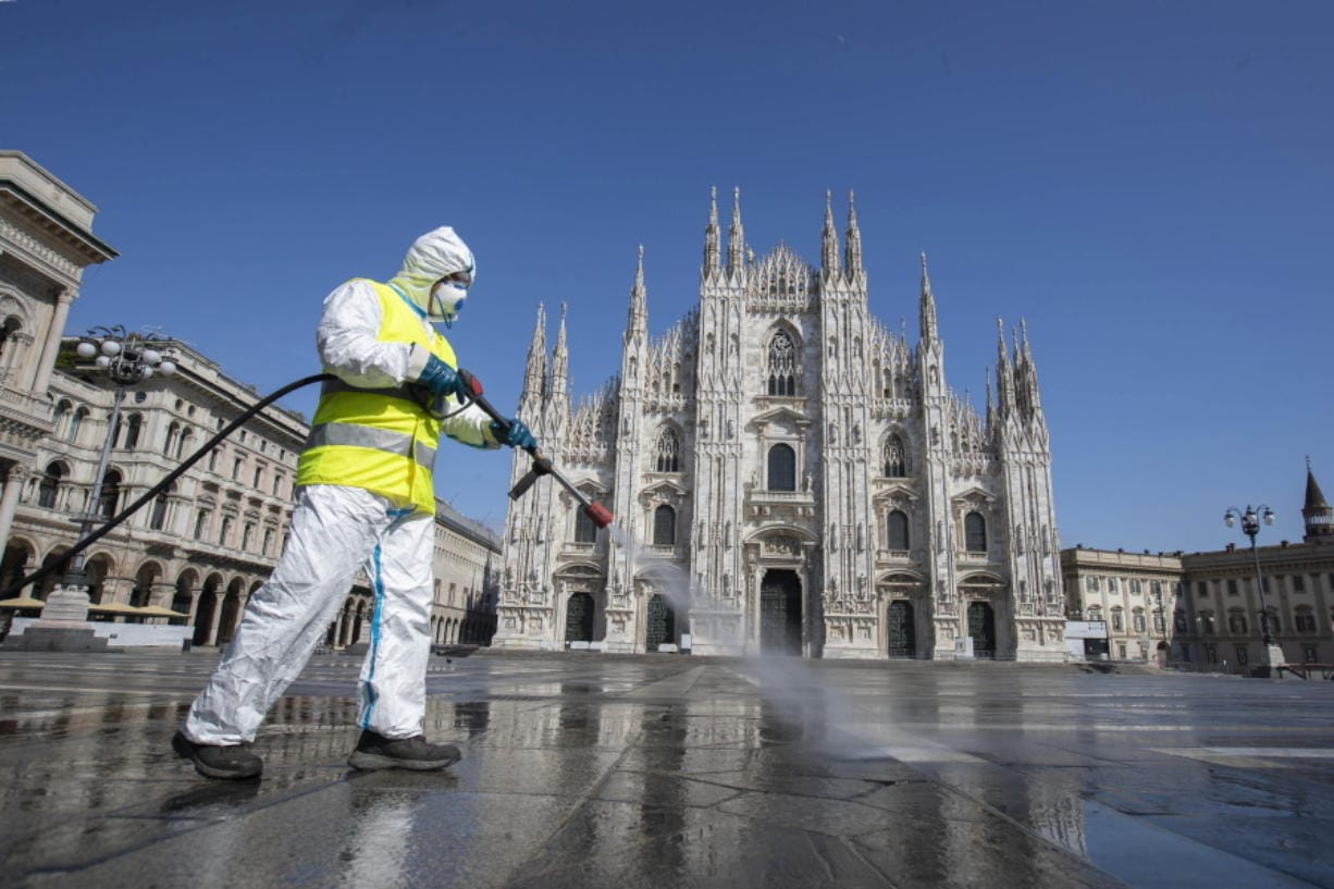 A worker sprays disinfectant to sanitize Duomo square, as the city main landmark, the gothic cathedral, stands out in background, in Milan, Italy, Tuesday, March 31, 2020. The new coronavirus causes mild or moderate symptoms for most people, but for some, especially older adults and people with existing health problems, it can cause more severe illness or death.