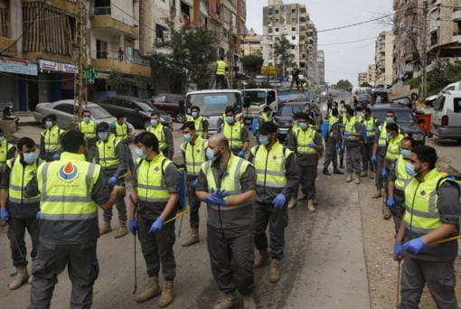 In this Friday, March 27, 2020 photo, members of the Islamic Health Society, an arm of the Iran-backed militant Hezbollah group prepare to spray disinfectant as a precaution against the coronavirus, in a southern suburb of Beirut, Lebanon. Hezbollah has mobilized the organizational might it once deployed to fight Israel or in Syria's civil war to battle the spread of the novel coronavirus. It aims to send a clear message to its Shiite supporters that it is a force to rely on in times of crisis -- particularly after it suffered a series of blows to its prestige. Opponents angrily accuse Hezbollah of helping bring the outbreak to Lebanon, saying it delayed a halt of flights from Iran for weeks after a woman who had just arrived from Iran emerged as Lebanon's first confirmed coronavirus case.