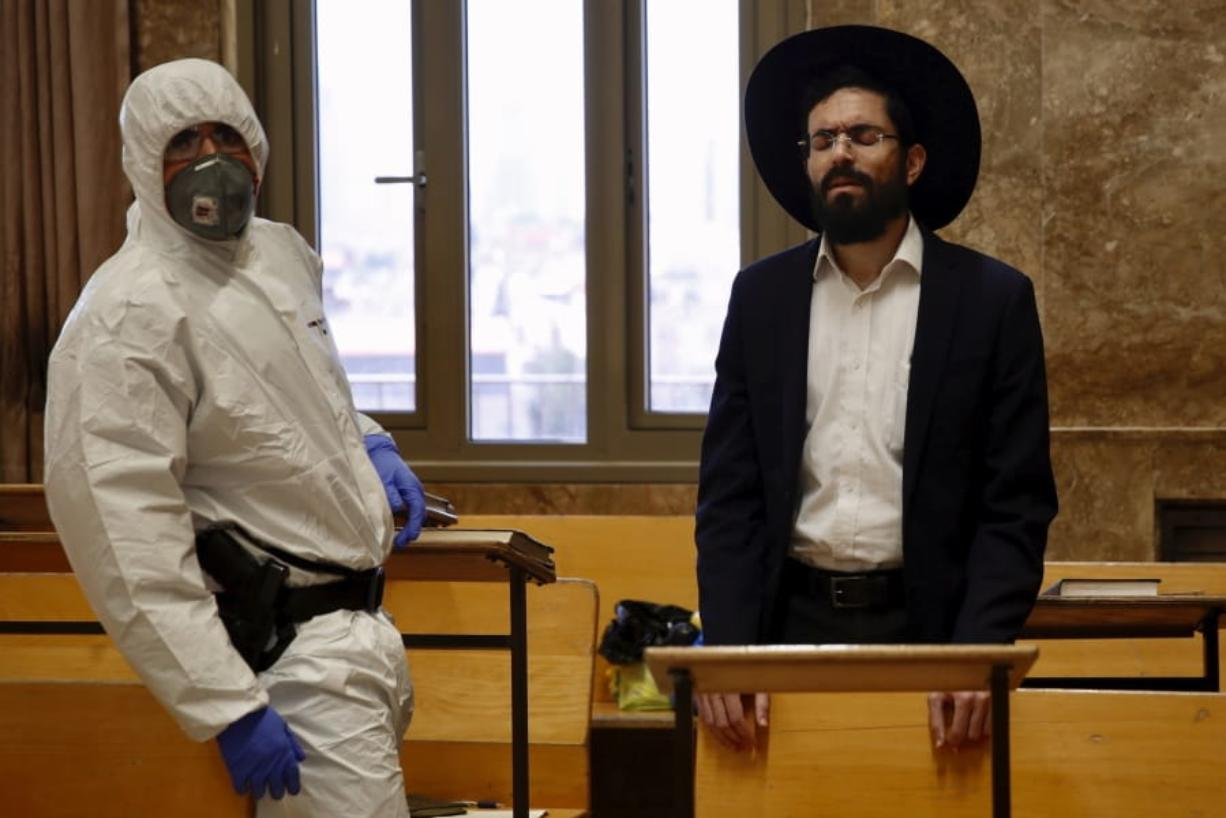 An Israeli police officer wearing protective gear waits to detain an ultra-Orthodox man as he prays in a synagogue because of the government's measures to help stop the spread of the coronavirus, in Bnei Brak, a suburb of Tel Aviv, Israel, Thursday, April 2, 2020. ?On Wednesday, Israeli Prime Minister Benjamin Netanyahu ordered a police cordon around the largely ultra-Orthodox city of Bnei Brak, to limit movement to and from the city. Bnei Brak has the second highest number of coronavirus cases in Israel.