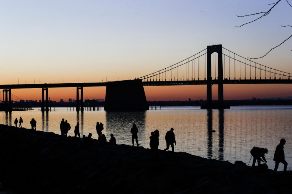 """People gather to watch the sun set behind the Throgs Neck Bridge at LIttle Bay Park Wednesday, April 8, 2020, in the Queens borough of New York. While New York Gov. Andrew Cuomo said New York could be reaching a """"plateau"""" in hospitalizations, he warned that gains are dependent on people continuing to practice social distancing."""