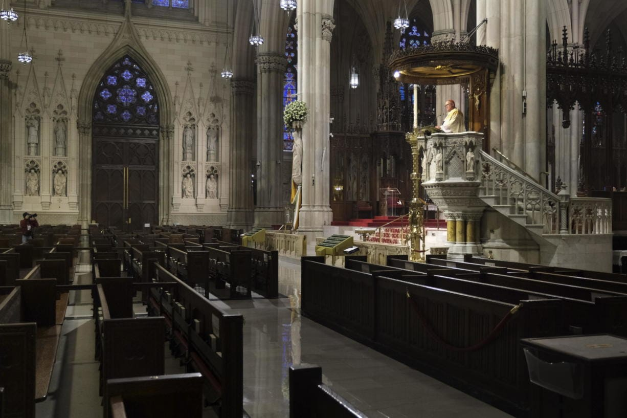 Archbishop Timothy Dolan, right, delivers his homily over empty pews as he leads an Easter Mass at St. Patrick's Cathedral in New York, Sunday, April 12, 2020. Due to coronavirus concerns, no congregants were allowed to attend the Mass but it was broadcast live on a local TV station.