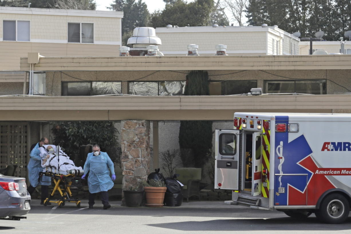 A person is loaded into an ambulance at Life Care Center in Kirkland, which has been at the center of the COVID-19 coronavirus outbreak in the state. Residents of assisted living facilities and their loved ones are facing a grim situation as the coronavirus spreads across the country, placing elderly people especially at risk. (AP Photo/Ted S.