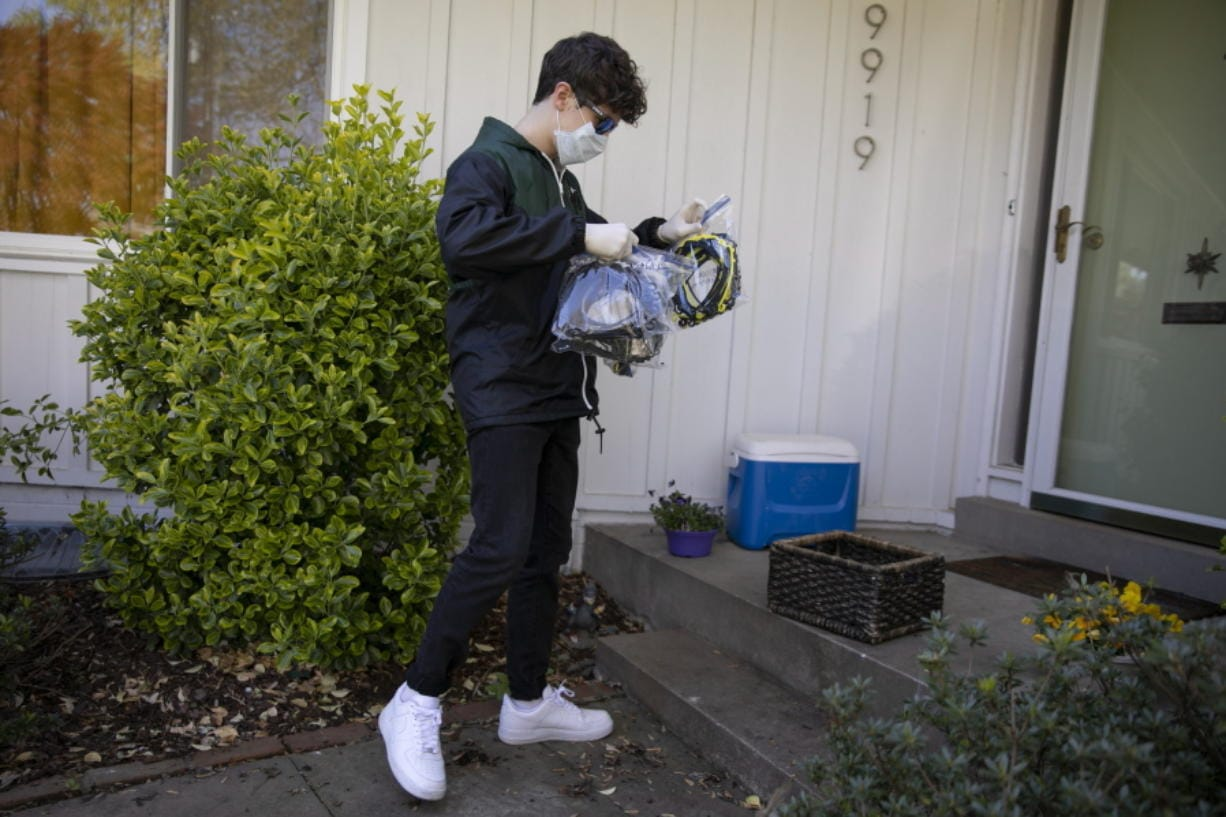 High school junior, Will Olsen, 17, of Kensington, Md., picks up bags holding pieces for medical face shields that were printed using personal 3D printers, in Kensington, Md., Sunday, April 19, 2020. He then delivered the bags to the Eaton Hotel in downtown Washington for assembly.