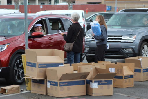 """FILE - In this March 26, 2020, file photo, people from Salem Health Hospitals & Clinics, hand out kits to make surgical masks causing a traffic jam in Salem, Ore., Thursday, March 26, 2020. Hospital workers in Oregon are astounded at the community response to an effort to provide those on the front lines of the coronavirus fight with protective masks. By Friday, April, 3, 2020, the last day for drop-off, 10,942 assembled masks had been returned. """"It's incredible to see the community come together and put in their time and effort to protect our health care workers during this time,"""" said Elijah Tanner, a Salem Health spokesman. (AP Photo/Andrew Selsky,File)"""