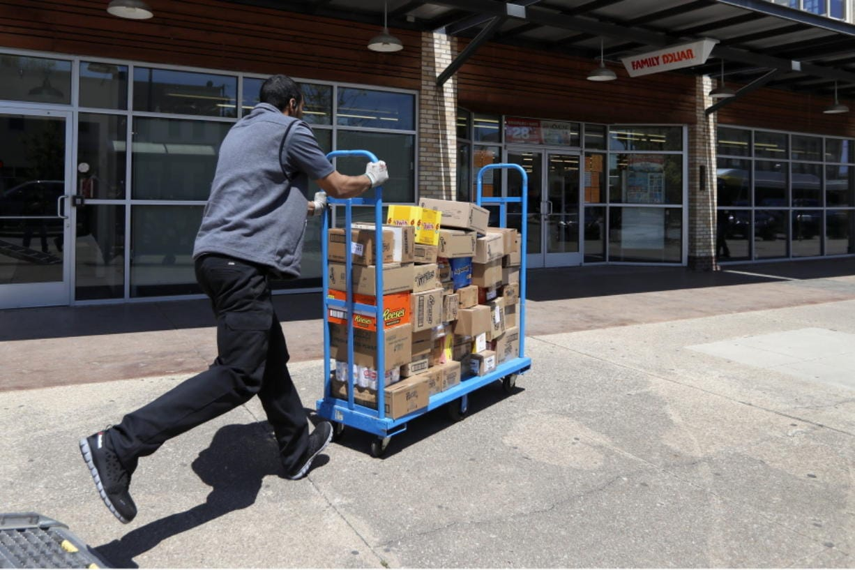 Cameron Webb, an employee with McLane Company, makes a delivery to a Family Dollar in Dallas, Wednesday, April 15, 2020.