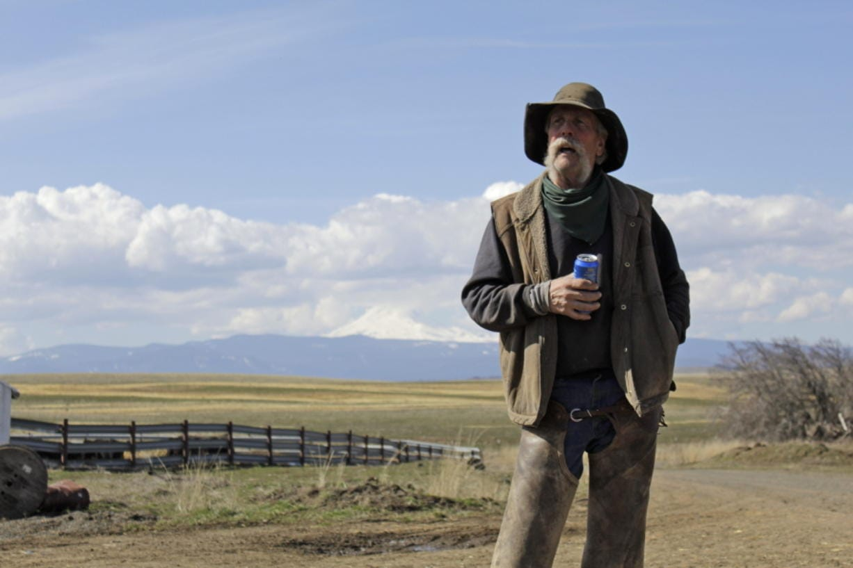 In this photo taken March 20, 2020, cattle rancher Mike Filbin stands on his property in Dufur, Ore., after herding some cows and talks about the impact the new coronavirus is having on his rural community. Tiny towns tucked into Oregon's windswept plains and cattle ranches miles from anywhere in South Dakota might not have had a single case of the new coronavirus yet, but their residents fear the spread of the disease to areas with scarce medical resources, the social isolation that comes when the only diner in town closes its doors and the economic free fall that's already hitting them hard.