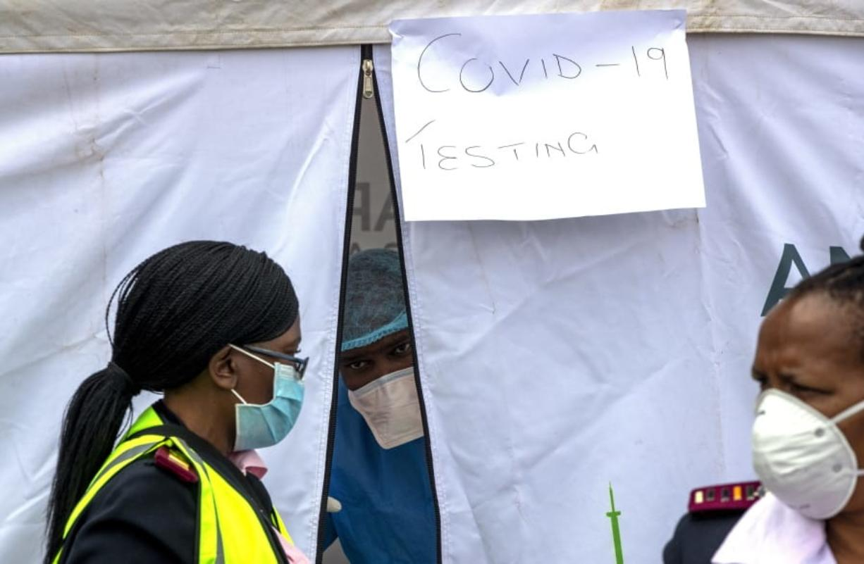 A health worker wearing personal protective gear inside a testing tent, gestures colleagues during the screening and testing for COVID-19, in Lenasia, south of Johannesburg, South Africa, Wednesday, April 8, 2020. South Africa and more than half of Africa's 54 countries have imposed lockdowns, curfews, travel bans or other restrictions to try to contain the spread of COVID-19. The new coronavirus causes mild or moderate symptoms for most people, but for some, especially older adults and people with existing health problems, it can cause more severe illness or death.