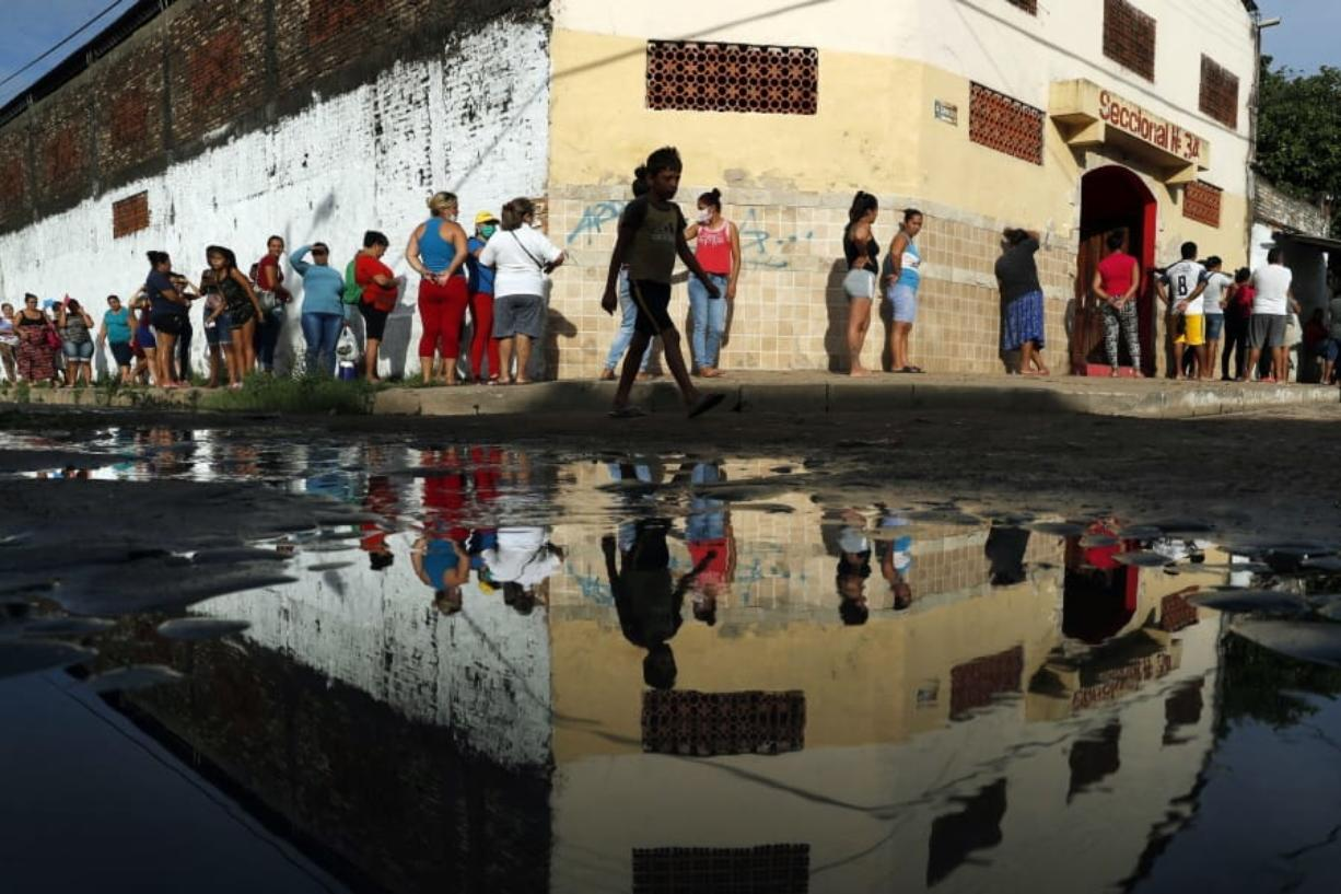 FILE - In this Tuesday, March 31, 2020 file photo, neighbors line up for free food staples outside Santa Ana primary school in Asuncion, Paraguay, part of an already existing food program through the Education Ministry, as people stay home from work amid the spread of the COVID-19 coronavirus. According to research released on Wednesday, April 1, 2020, more evidence is emerging that coronavirus infections are being spread by people who have no clear symptoms, complicating efforts to gain control of the pandemic.