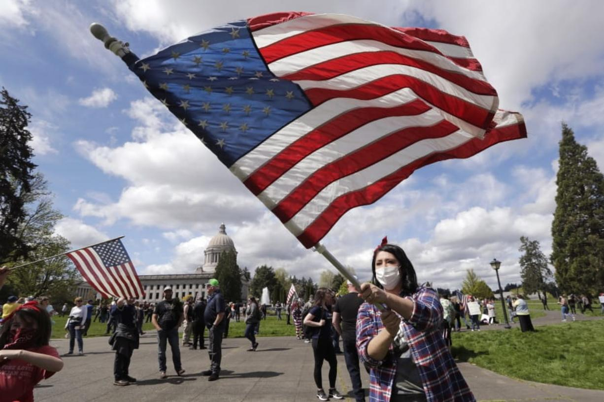 Janell Sorensen of Woodland waves a flag as demonstrators gather at the Capitol in Olympia to oppose Washington's stay-home order to slow the coronavirus outbreak Sunday. State Rep. Vicki Kraft, R-Vancouver, was also in attendance to support the protest.
