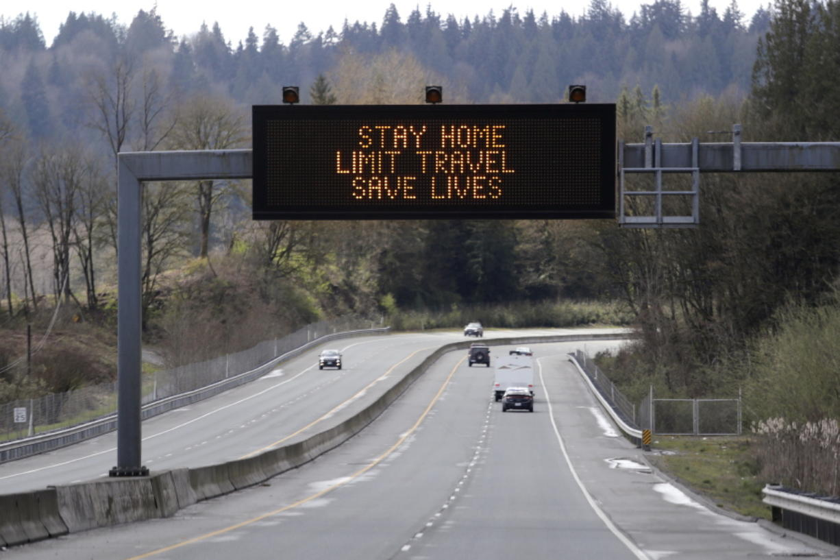 "A sign overhead on an unusually quiet highway reminds drivers to ""Stay home, limit travel, save lives"" as part of Gov. Jay Inslee's ongoing stay-at-home order in the midst of the coronavirus outbreak, Wednesday, April 1, 2020, in Monroe, Wash."