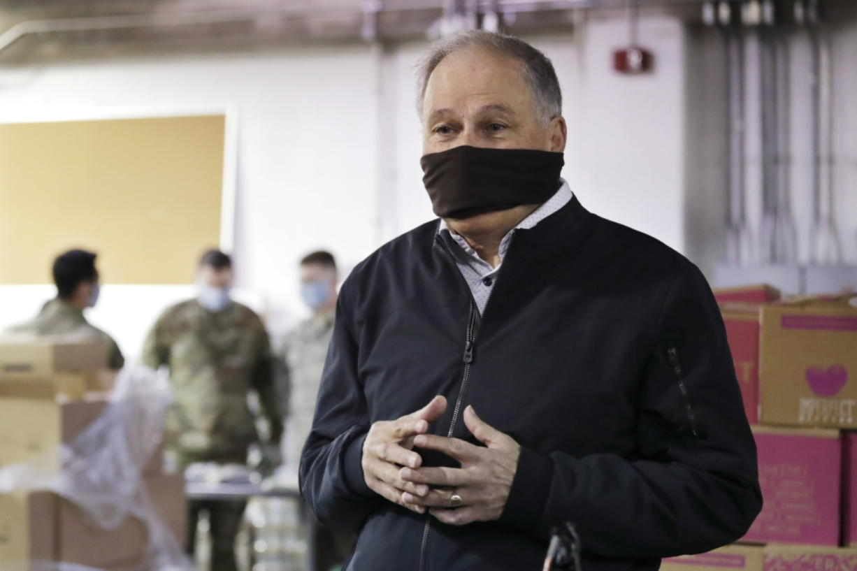 Gov. Jay Inslee wears a makeshift mask as he speaks with media members while visiting inside Nourish Pierce County warehouse, where Washington National Guard members were packing food in response to the coronavirus outbreak Friday in Lakewood.