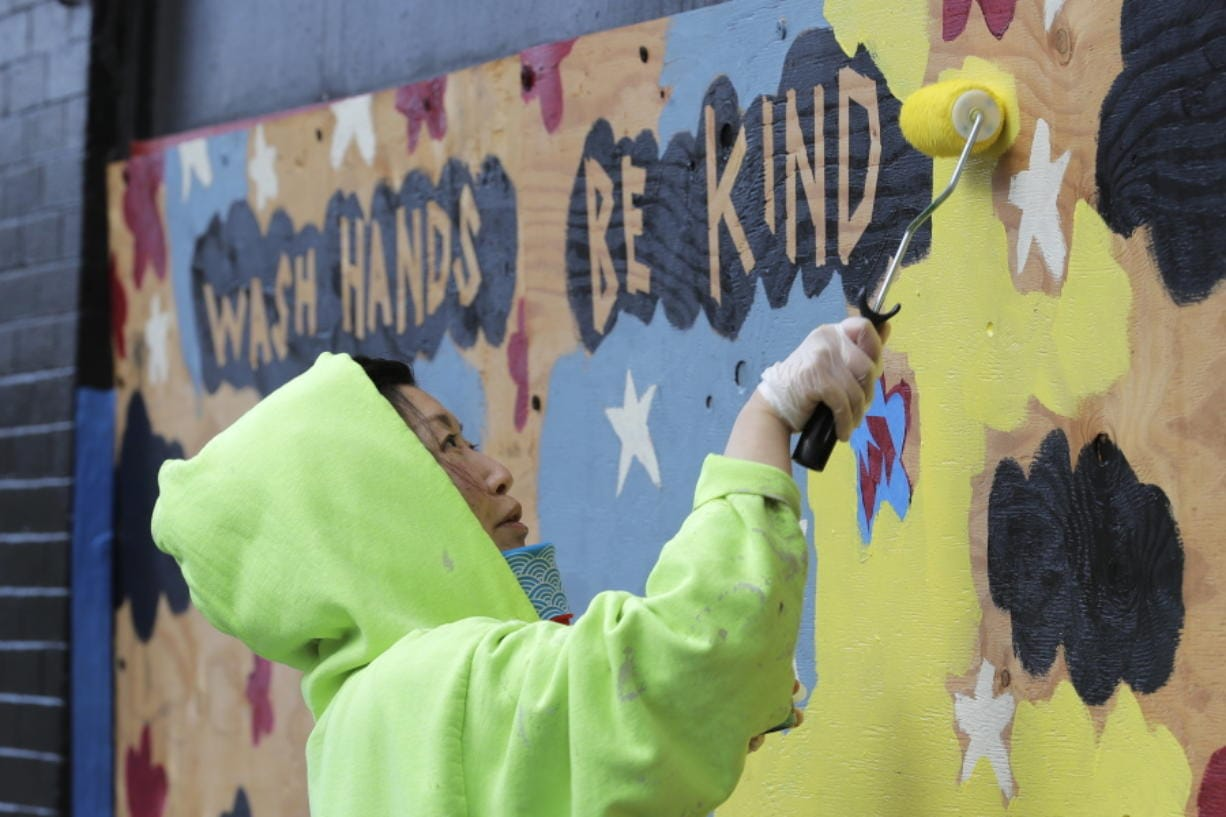 """Momo Nikaido paints a mural that reads """"wash hands, be kind,"""" Wednesday, April 1, 2020, on boards over windows of the Capitol Lounge, which is owned by her father in Seattle's Capitol Hill neighborhood. Most stores and businesses in the area are closed or only offering take-out food as a result of the outbreak of the new coronavirus, and state-wide stay-at-home orders from government officials. (AP Photo/Ted S."""