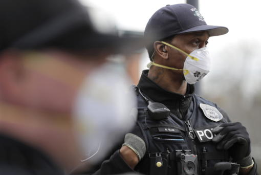 Seattle Police officer Rosell Ellis, right, wears an N95 mask as he listens to conversation during a routine call Thursday, April 2, 2020, in Seattle. As police and fire departments across the country face personnel shortages due to the spread of the new coronavirus, masks and other protective gear are being used to keep officers and firefighters still on the streets safe and healthy. (AP Photo/Ted S.