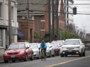 A cyclist rides along Columbia Street in February 2019. A project to remove street parking and add bike lanes has been postponed.