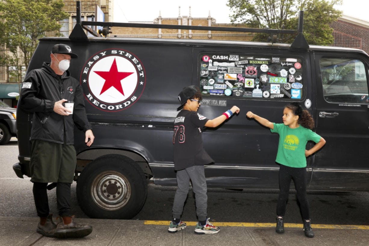 From left: Easy Street Records owner Matt Vaughan is seen with his out-of-school kids Archie, 8; and Daisy, 6, Thursday April 30, 2020 in West Seattle during the coronavirus outbreak. Vaughan, who makes home deliveries of records, credits an extremely loyal customer base and said most of what the store moves are vinyl LPs, which outsell merch and CDs.
