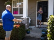 Mountain View High School teacher and coach Dan Larson uses a fishing pole to drop off materials for a fishing license for senior Abby Horton at her home in Vancouver. Larson asked his senior students to all tell him a small thing they wished for that he could help come true. Throughout the last few weeks he's been completing one of these small acts of kindness for at least one of his students a day.