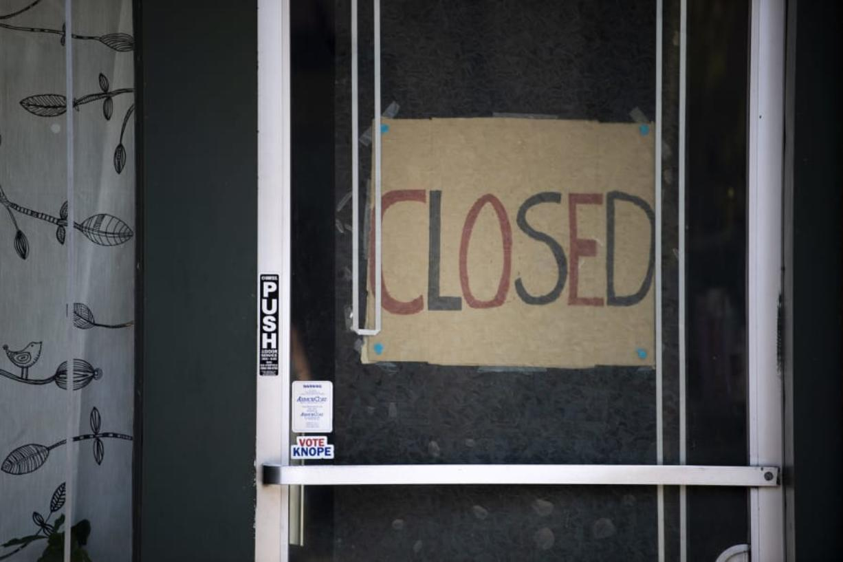 A closed sign is pictured in the door of Simple Solitude in Vancouver on April 20.