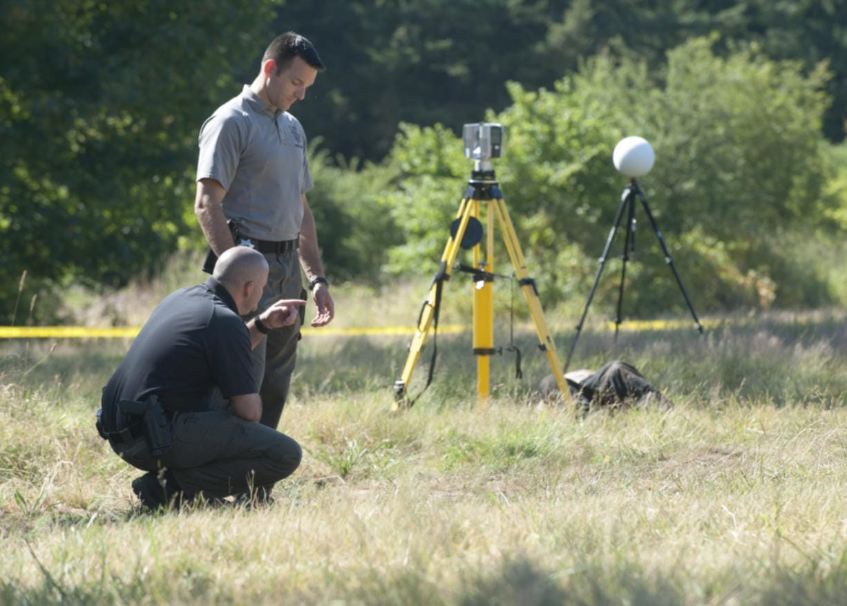 Detectives Joe Swenson, left, and Scott Gilberti investigae at the scene of a homocide in Ridgefield Wednesday July 1, 2015. The body of a man was dumped in a field off 179st Street in Ridgefield.
