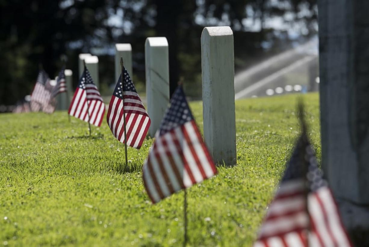 Afternoon sun illuminates American flags placed in preparation for Memorial Day at Vancouver Barracks Post Cemetery on May 23, 2019.