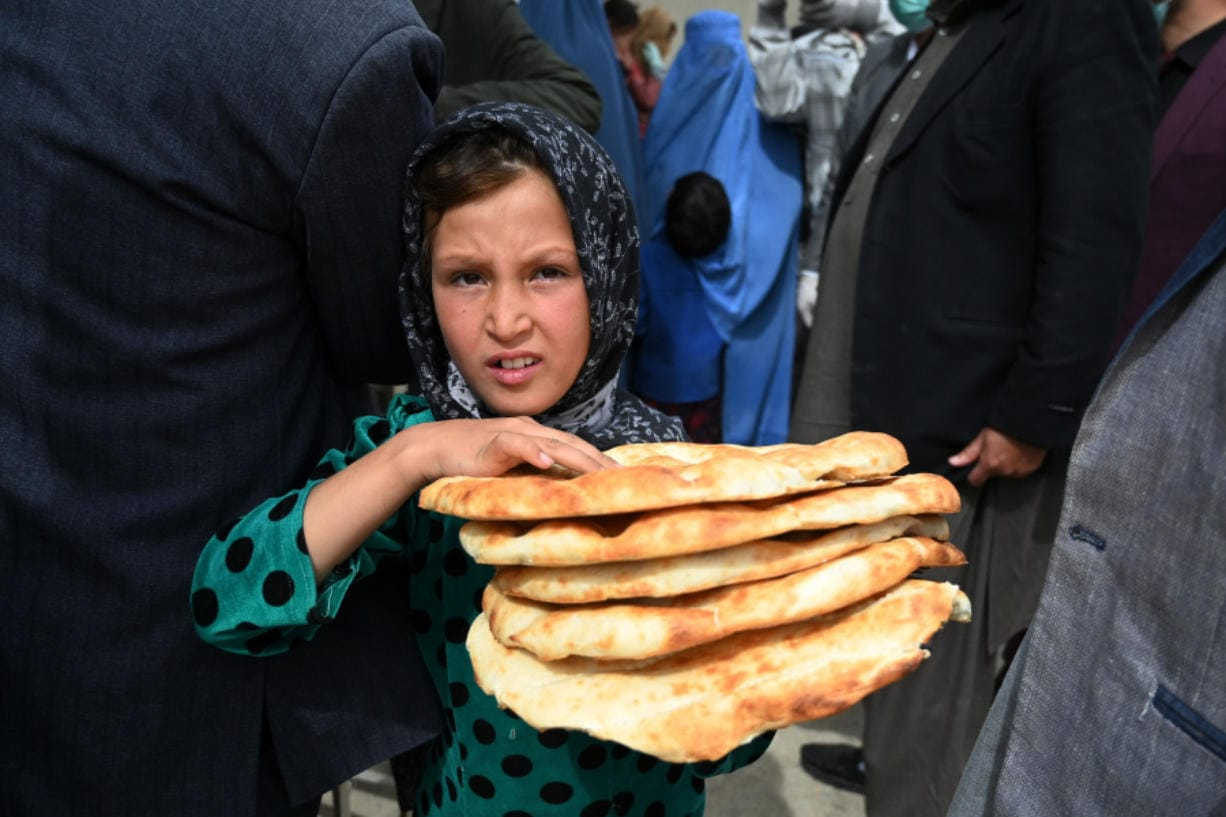 A young girl leaves after receiving free bread from the municipality outside a bakery during the Islamic holy month of Ramadan as government-imposed a nationwide lockdown as a preventive measure against the COVID-19 coronavirus, in Kabul on April 29, 2020.