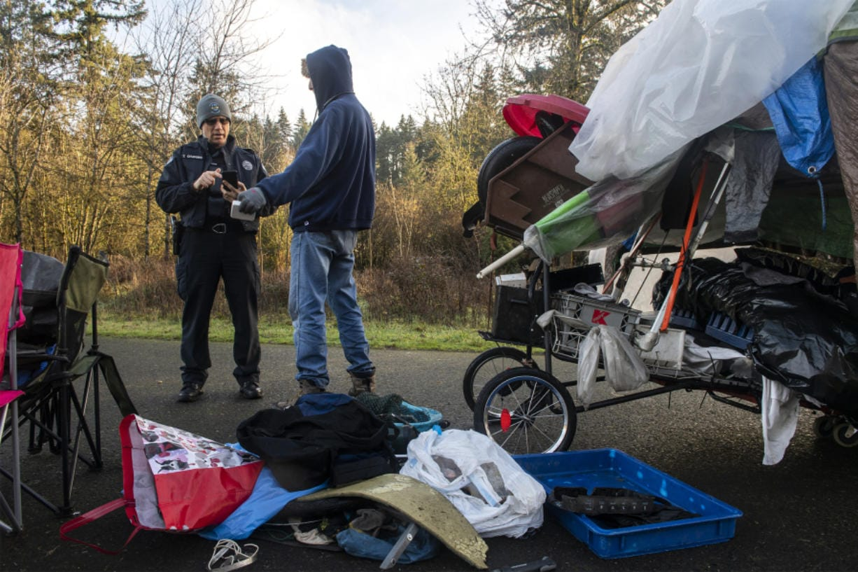 Tyler Chavers, Vancouver's homeless assistance response team officer, left, talks with Shawn Fernandez during the 2020 Point in Time count near Leverich Park on Jan. 30.