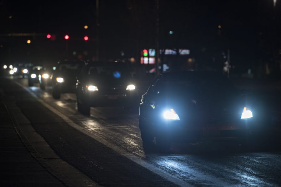 Motorists with bright headlights navigate an intersection near Vancouver Mall.