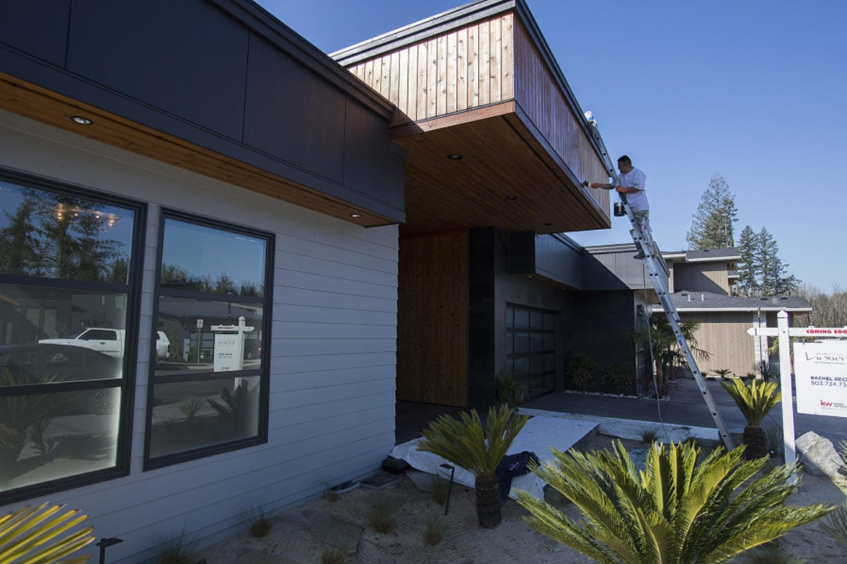 Jose Ramirez of Gecho Construction adds a fresh coat of stain to a new home at The Parklands in Camas in late March, as the impact of the novel coronavirus pandemic began to be felt. Home sales fell dramatically in the following month.
