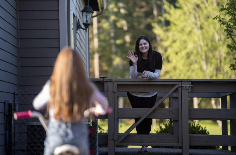 Melanie Zaytsev, 7, rides her bike and visits with her mother, Tiona Gudishvili, at their home in Vancouver. Gudishvili, an ICU nurse, socially distanced herself from her family while she treated a flurry of COVID-19 patients.