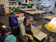 Second-grade teacher Nicole McClennen is joined by some furry friends as she records a lesson for her students on a laptop at Green Mountain School. McClennen said she tries to keep her video lessons familiar, and records them in her classroom's cozy reading corner.