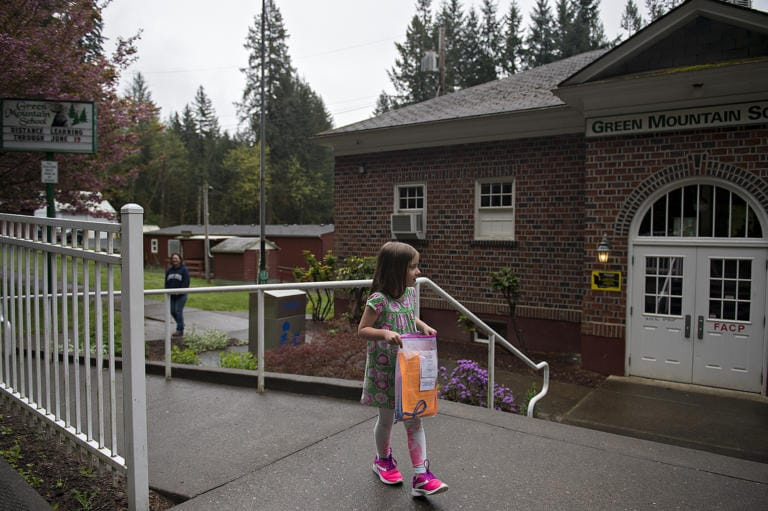 Green Mountain School first-grader Kolbie Bennett, 7, takes the school packet with her assignments to go while visiting the closed campus with her mom, Aeranee, in Woodland on Friday morning, April 24, 2020.