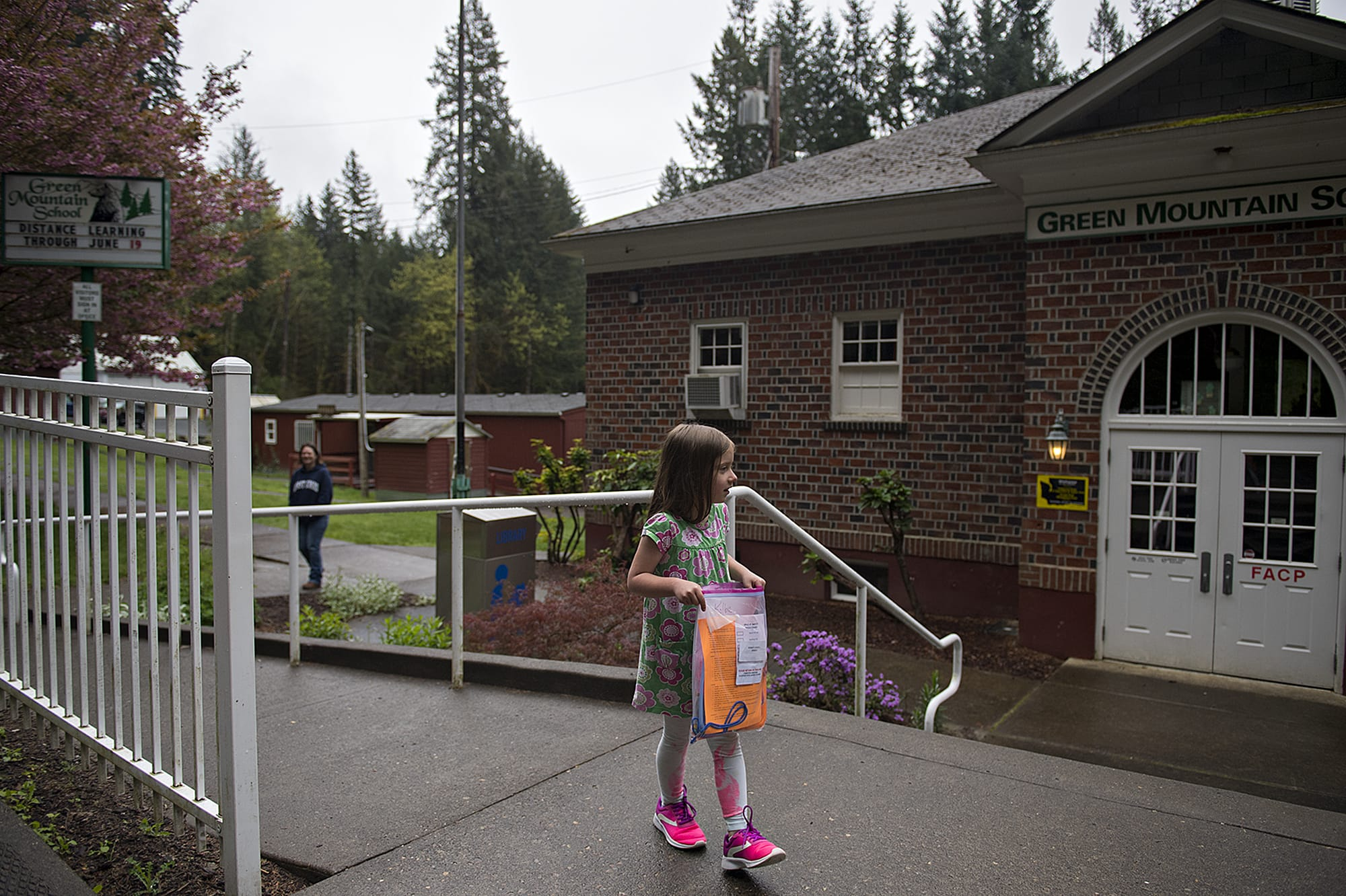 Green Mountain School first-grader Kolbie Bennett, 7, takes the school packet with her assignments to go while visiting the closed campus with her mom, Aeranee, in Woodland on Friday morning, April 24, 2020. (Amanda Cowan/The Columbian)