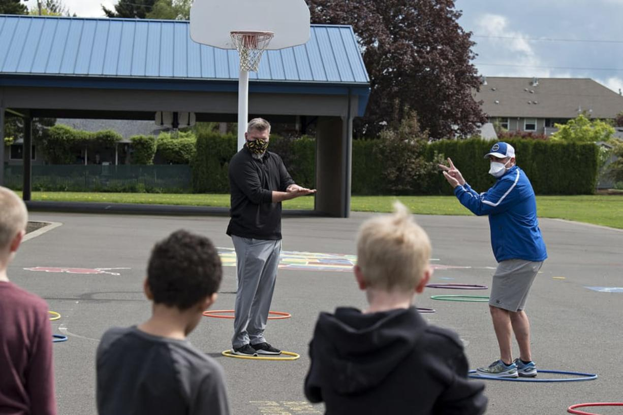 Union's Rory Rosenbach, left, and Mountain View's Adam Mathieson demonstrate how to navigate through a game that involves no contact and rock, paper, scissors for youngsters at Crestline Elementary School on Monday afternoon, April 27, 2020.