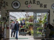 Vancouver resident Rich Packer, right in blue hat, joins fellow shoppers as they look to brighten up their homes with flowers and plants at Yard 'n Garden Land on Tuesday. The business has been experiencing a boost in sales in recent months due to shoppers turning to home garden projects during the pandemic.