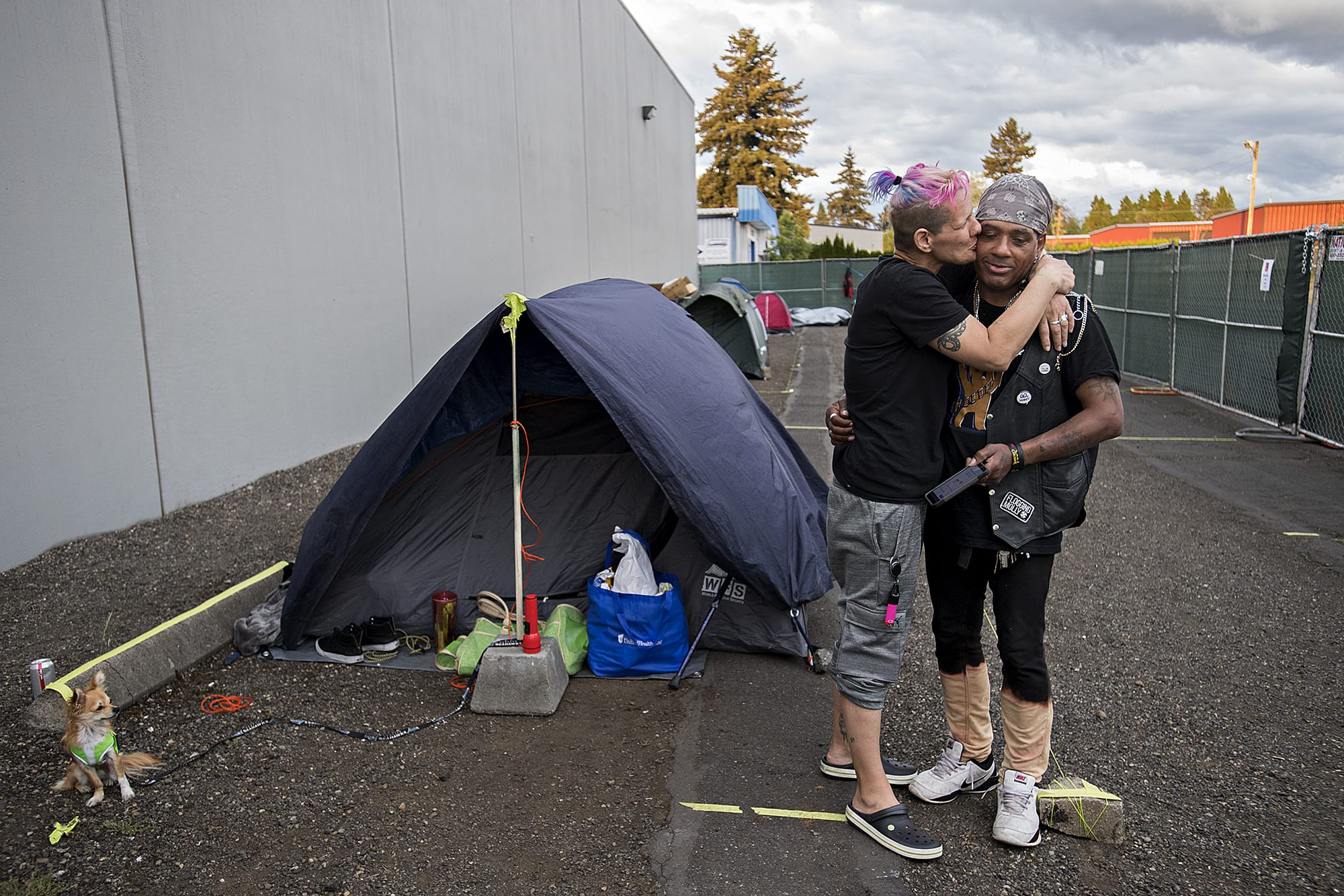 Mandi Holper, left, and Chris Winston share a quiet moment as they prepare to settle in for the night at the temporary homeless encampment outside Living Hope Church on Tuesday evening, May 5, 2020. (Amanda Cowan/The Columbian)
