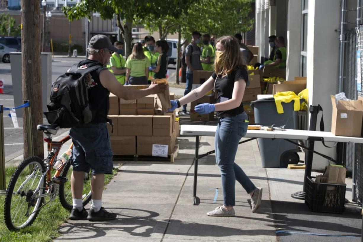 Volunteer Carlie Shoup, right, hands a sack lunch to a passerby at the FISH Westside Food Pantry in downtown Vancouver on Saturday morning. Most clients drove up and had food boxes and bags placed directly into the trunks of their cars, with no social contact necessary.