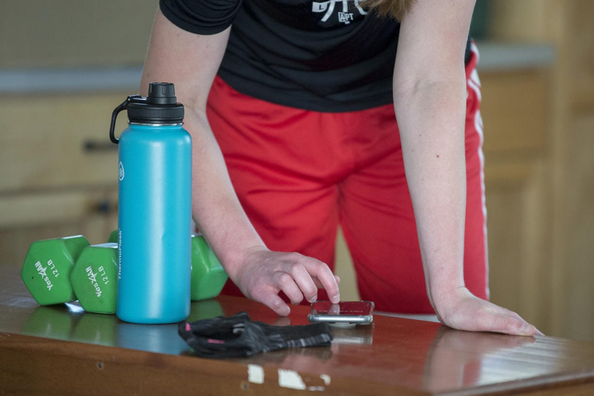 Faith Bergstrom of Camas gets instructions from her coach via smartphone as she works out in her family's garage during the COVID-19 pandemic Friday morning, May 8, 2020.