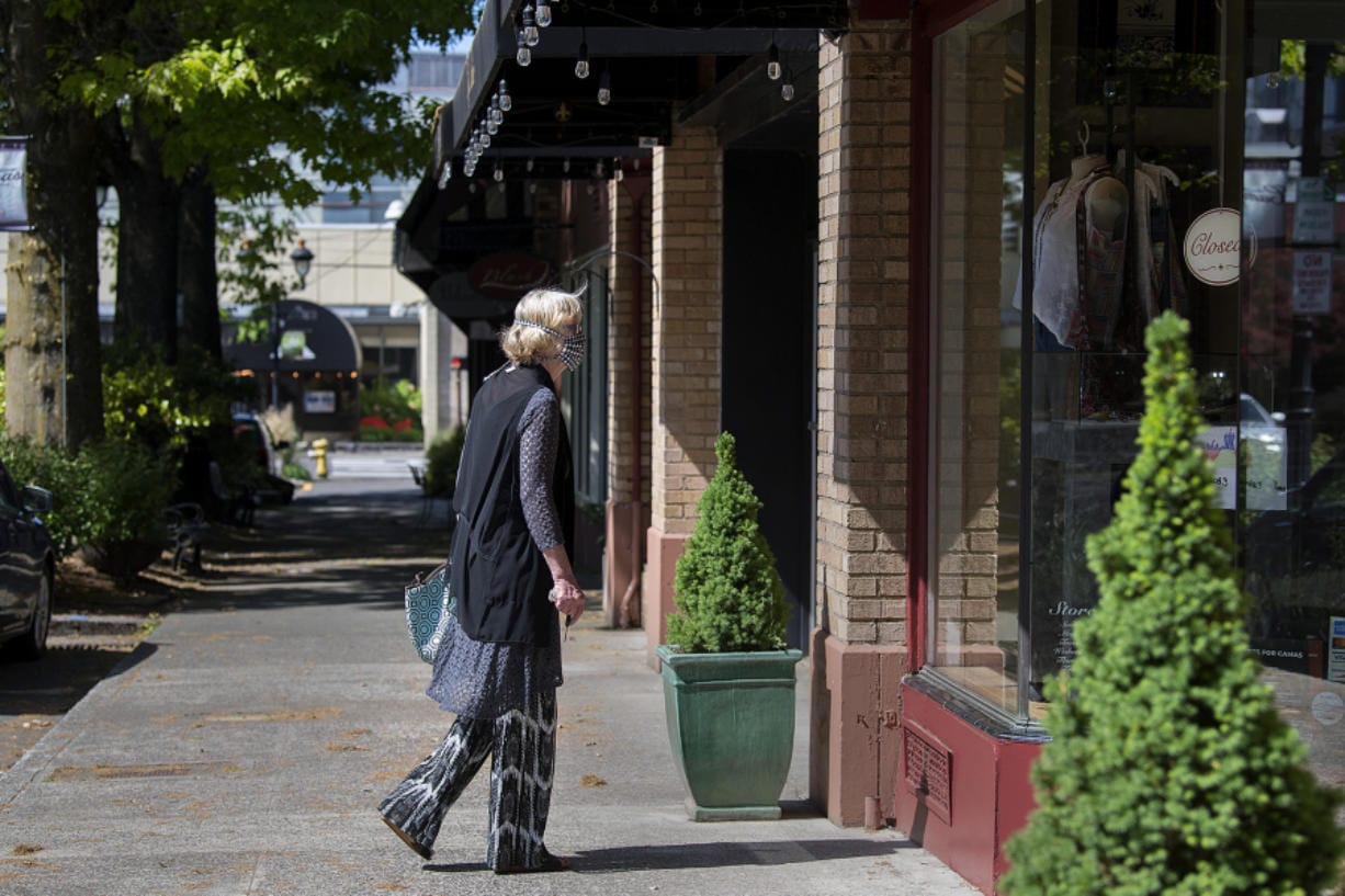 Uta Zuendel, who has lived in Camas since 1974, pauses to check out a window display of a closed boutique as she strolls through a nearly empty Main Street in downtown Camas on May 7.