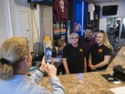 Marykay Lamoureaux, left, executive director of Ridgefield Main Street, records a video of Tammy Curlett, owner of Three-Sixty Burgers & Brews, and her children, Robert and Breeanna Skeffington, on Friday afternooon as they encourage residents to shop locally.