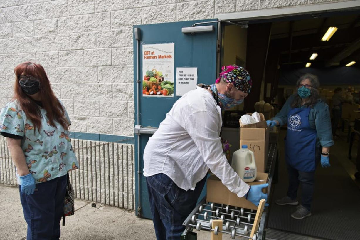 Elizabeth Bell, who works as an individual provider in Vancouver, from left, waits to pick up food for a client as Nicholas Chandler, also of Vancouver, picks up food off a conveyer belt with the help of volunteer Maggie Bomber of St. Vincent de Paul Vancouver on Thursday morning. St. Vincent de Paul Vancouver has been one of the busiest food pantries during the pandemic.