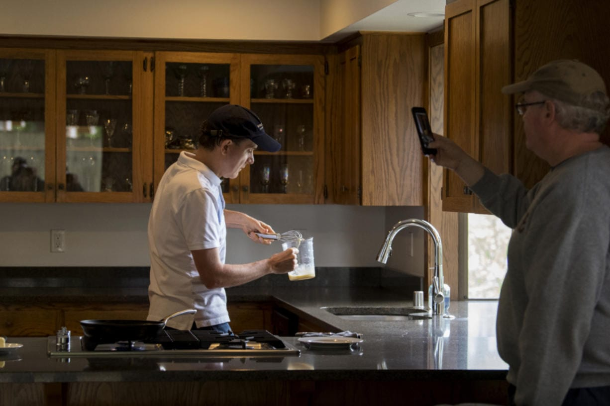 Volunteer Kevin Danley, left, whips up some scrambled eggs while making an instructional video with his partner, Kevin McClure, at their Vancouver home. Danley records several instructional cooking videos a week for students at the Washington State School for the Blind.