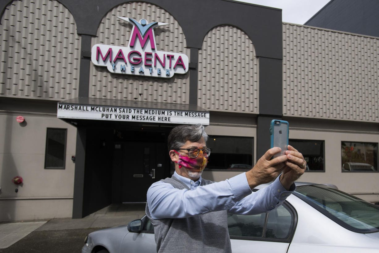 Sound technician Peter Wonderly wears a mask for safety as he snaps a selfie after putting the finishing touches on the front sign at the Magenta Theater in downtown Vancouver on Friday. Magenta Theater, which is dark during the COVID-19 pandemic, came up with the idea of renting out its Main Street marquee for community messages.