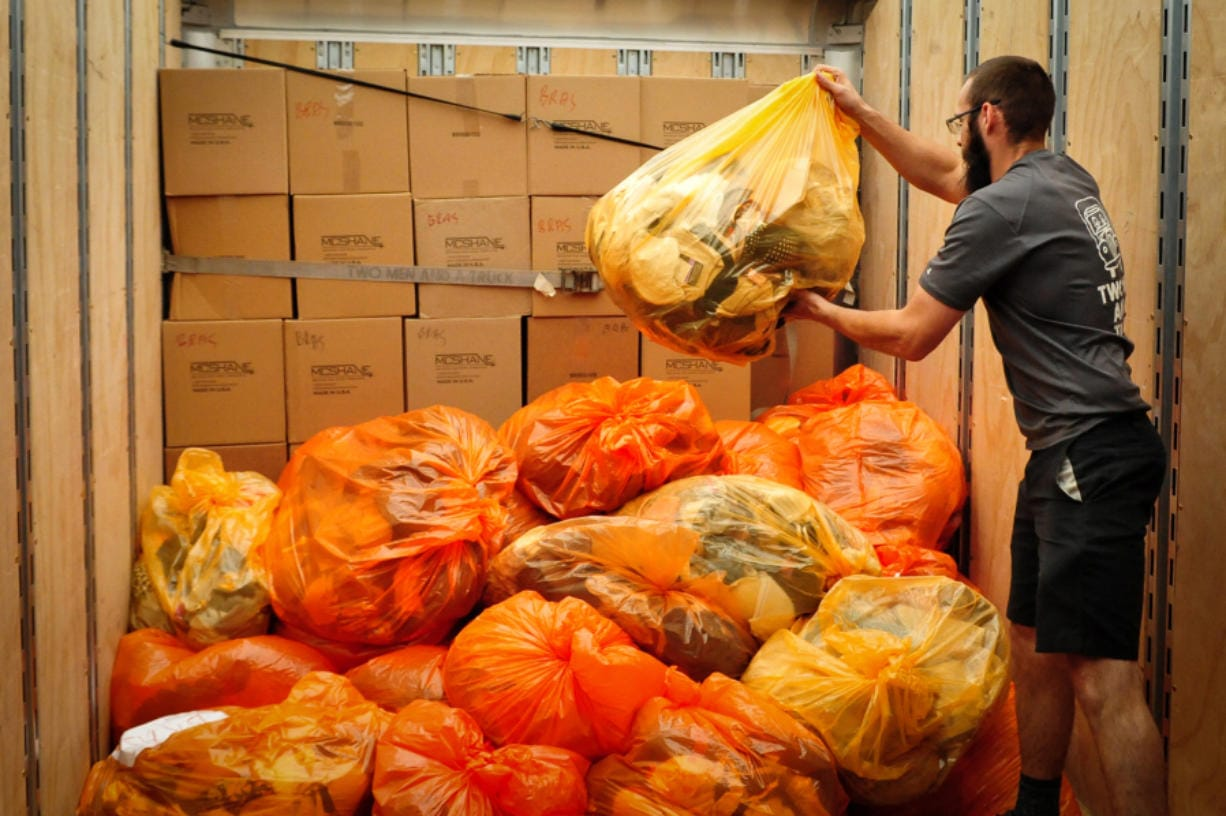 Dylan Denault, a driver with Two Men and a Truck, loads 5,000 bras donated from Ridwell in Seattle last week. Ridwell collected the bras for the National Women's Coalition Against Violence & Exploitation in Vancouver.