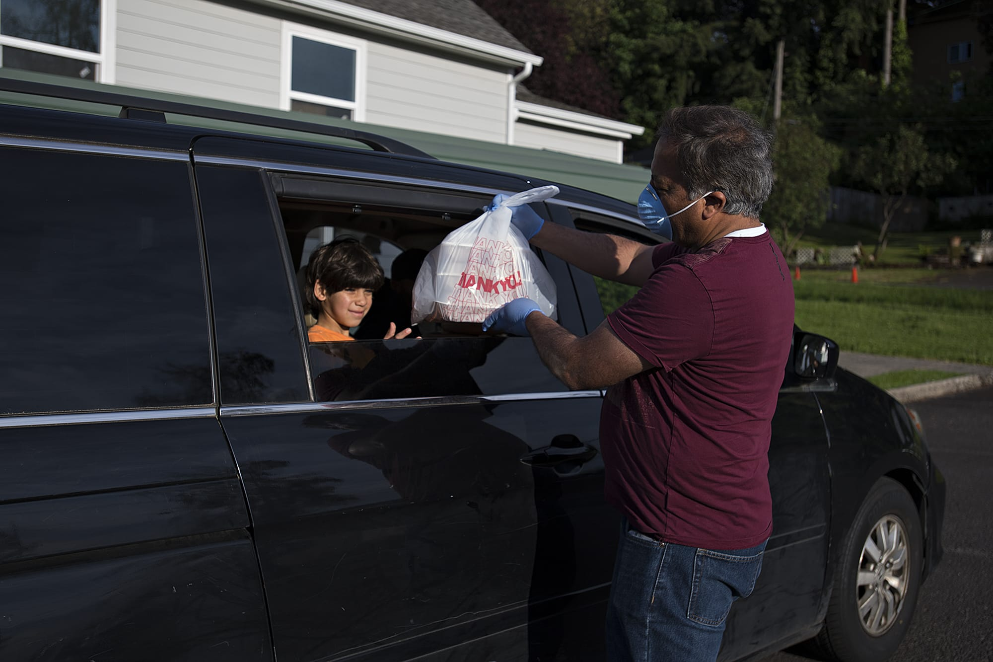 Abdullah Hariri, 7, left, helps collect meals for his family from treasurer Ahmad Qayoumi at the Islamic Society of Southwest Washington on Sunday evening, May 17, 2020. The local mosque is doing meals-to-go for Ramadan this year because of concerns about COVID-19.