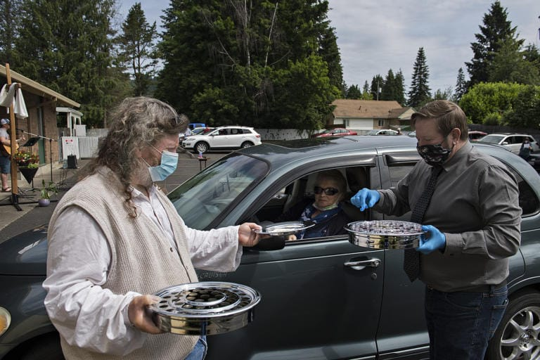 Charlie Raetz, left, a longtime member of St. Matthew Lutheran Church in Washougal, offers communion to Camas resident Tanya Fritz with the help of Pastor Robert Barber on Sunday morning, May 24, 2020. St. Matthew Lutheran Church, a small church in Washougal, offered its first drive-in church service that also included music, a message and cookies to-go for those in attendance.