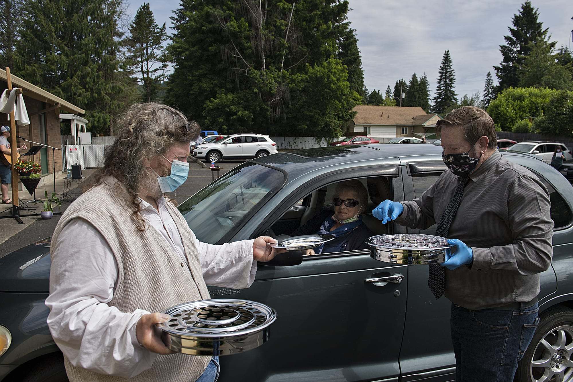 Charlie Raetz, left, a longtime member of St. Matthew Lutheran Church in Washougal, offers communion to Camas resident Tanya Fritz with the help of Pastor Robert Barber on Sunday morning, May 24, 2020. St. Matthew Lutheran Church, a small church in Washougal, offered its first drive-in church service that also included music, a message and cookies to-go for those in attendance. (Amanda Cowan/The Columbian)